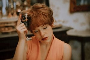 Image of a woman holding an empty wine glass to her forehead.