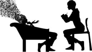 Silhouette of two seated figures. One is a therapist or counselor taking notes while the client talks. The client's head is disintegrating as she talks.