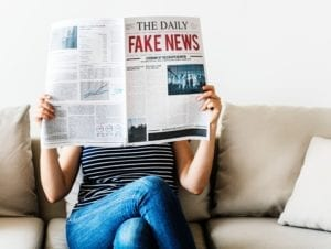 """Image of a woman reading a newspaper with the headline, """"FAKE NEWS."""""""