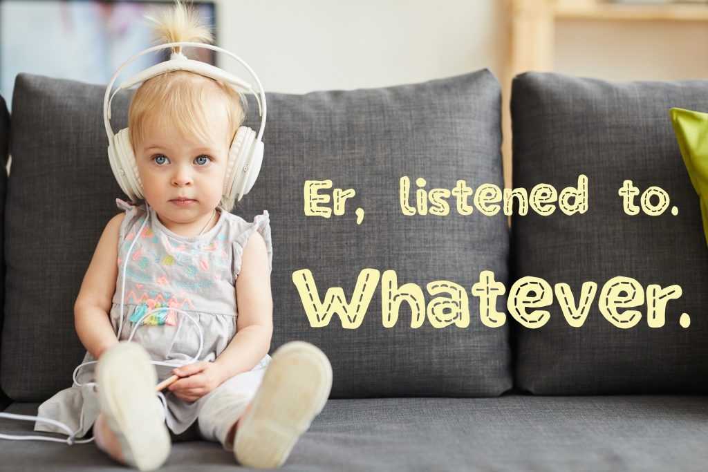 Serious little girl with blue eyes wearing gray dress sitting on sofa in living room and using smartphone to listen to audiobook in headphones. with text that says Er, listened to. Whatever.