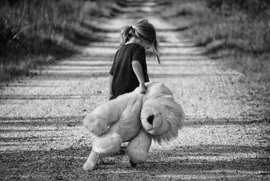 Black and white image of a small girl carrying a lion stuffed animal almost as big as she is walking away from the camera down a desolate road